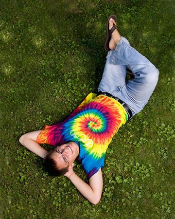 Man laying on grass in a tie-dye shirt